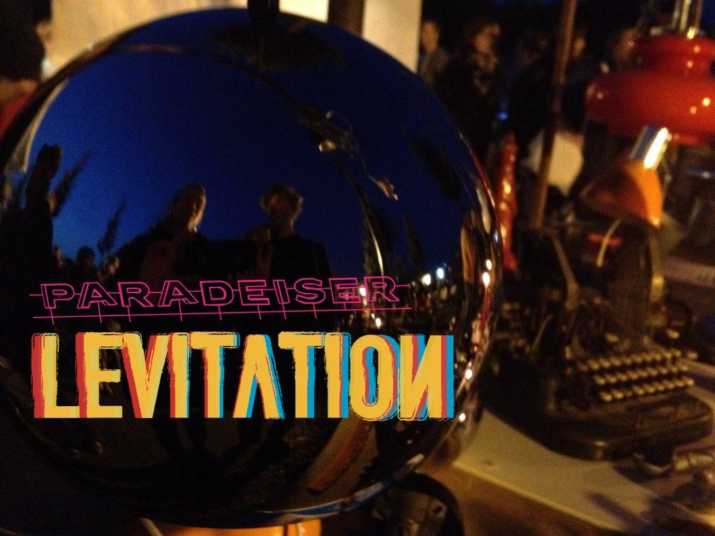 eine Spiegelkugel, eine Schreibmaschine und das Wort Levitation.